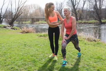 Senior woman with personal fitness trainer doing sport on meadow close to the water