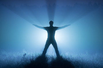 A foggy night. Blue tones. Silhouette of a man. A man raised his hands up. Spotlight behind a man