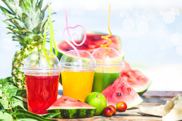 Bright Fresh healthy juices, fruit, pineapple, watermelon on the background of the sea. Summer, rest, healthy lifestyle Copy space