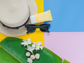 summer minimal and flat lay concept from white seashell and tropical flower decorate on banana leaf with beach hat ,sunglasses ,sun block lotion and colorful pastel style background