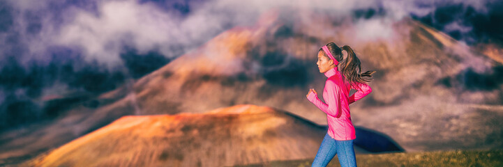 Running fit woman runner training on trail run outdoors in dramatic volcanic landscape. Panoramic banner header crop of Asian girl athlete exercising outside.