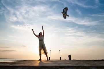 Happy young woman running with a kite on a beach at sunset in summer.