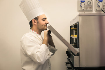 Pastry chef checking the oven