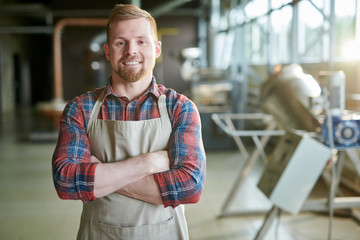 Waist up portrait of smiling bearded man wearing apron posing standing confidently with arms crossed against roasting machines in artisan coffee roastery, copy space