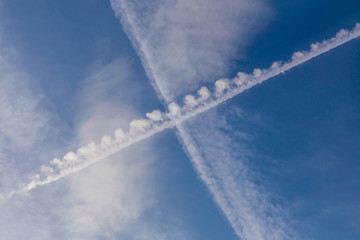 Inversion traces from aircraft. Cross in the sky.