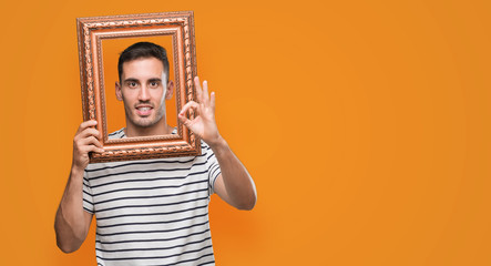 Handsome young man looking through vintage art frame doing ok sign with fingers, excellent symbol