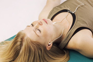 Beautiful young woman on a yoga mat relaxes, close-up