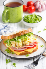 Ham sandwich with scrambled egg, cheese, tomato, lettuce, tasty healthy Breakfast on white wooden background