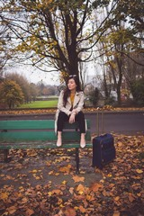 Businesswoman sitting on bench during autumn