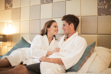 Couple sharing intimate moment in bed in a hotel.