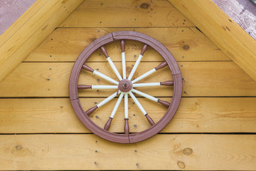 A hand-spinning wheel on the wall, half the roof