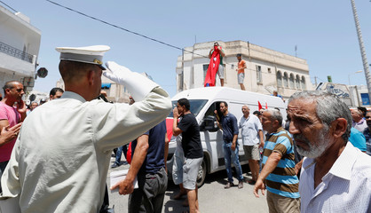 A policemen at attention in front of an ambulance carrying the coffin of Anis El Werghi, a Tunisian security forces member, who was killed in an ambush in the northwest of the country, during his funeral in Tunis
