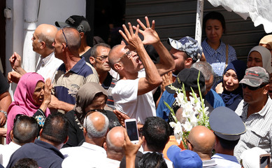 A man mourns Anis El Werghi, a Tunisian security forces member, who was killed in an ambush in the northwest of the country, during his funeral in Tunis