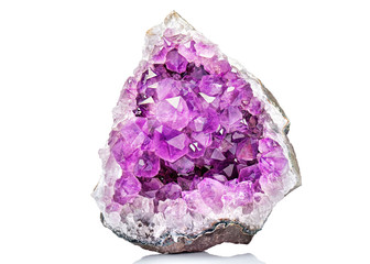 Violet Crystal Stone macro mineral. Purple rough Amethyst quartz crystals geode on white background, Uruguay