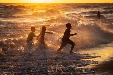 Three children splashing in ocean waves