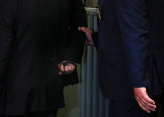 Film producer Harvey Weinstein is led handcuffed by police into his hearing at Manhattan Criminal Court in New York