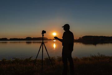 Silhouette vom Fotograf der den Sonnenuntergang Fotografiert