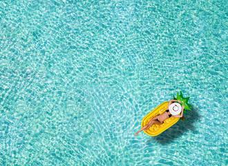 Junge, schlanke Frau im Bikini treibt auf einer Ananasförmigen Luftmatratze über die tropischen Gewässer der Malediven und genießt ihren Urlaub