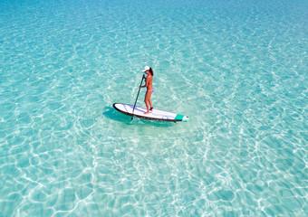 Frau im Bikini auf Stand Up Paddle Brett über türkisem Ozean auf den Malediven