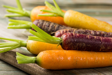 Fresh raw colorful carrots roots, purple, yellow and orange on old wooden table. Healthy food vegetable background.