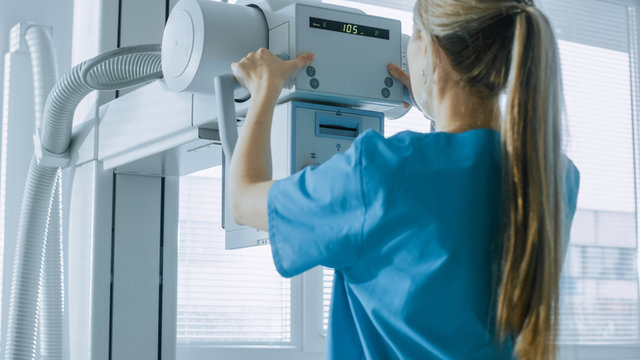 In the Hospital, Female Technician adjusts X-Ray Scanner / Machine. Modern Hospital with Technologically Advanced Medical Equipment and Professional Personnel.