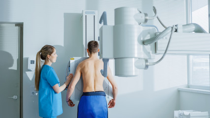 In the Hospital, Man Standing Face Against the Wall While Medical Technician Adjusts X-Ray Machine For Scanning. Scanning for Fractures, Broken Limbs, Chest, Cancer or Tumor. Modern Hospital.