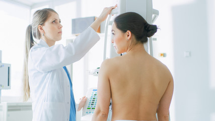 In the Hospital, Mammography Technologist / Doctor adjusts Mammogram Machine for a Female Patient. Modern Technologically Advanced Clinic with Professional Doctors. Breast Cancer Prevention Screening.