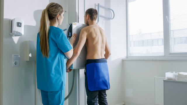 In the Hospital, Man Standing Face Against the Wall While Medical Technician Adjusts X-Ray Machine For Scanning. Scanning for Fractures, Broken Limbs, Chest, Cancer or Tumor. Modern Hospital