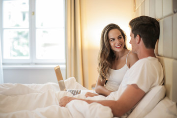 Couple in bed with laptop in a hotel
