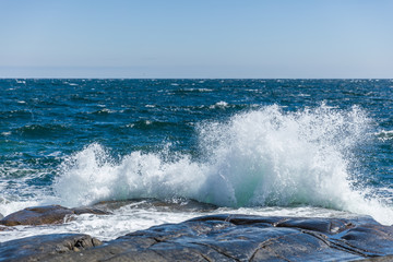 Waves splashing against the rocky seashore of Norway