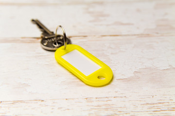Yellow key tag on a light tree textured background.The concept of renting, selling. Template. Trend colors
