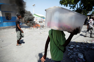 People walk past burning tires on a street of Port-au-Prince