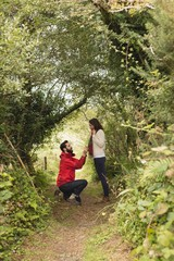 Side view of man proposing to woman in forest