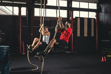 Two men doing rope climbing exercise