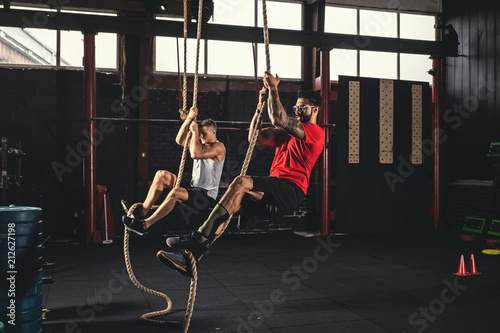 two men doing rope climbing exercise stock photo and royalty free