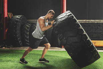 Strong sportsman doing  a tire flip exercise