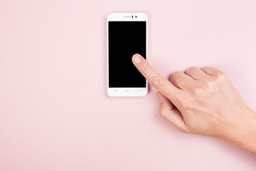 Hand with a smartphone on a pink background. Empty space. Finger