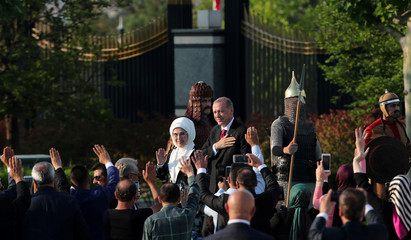 Turkish President Tayyip Erdogan, accompanied by his wife Emine Erdogan, arrives for a ceremony at the Presidential Palace in Ankara