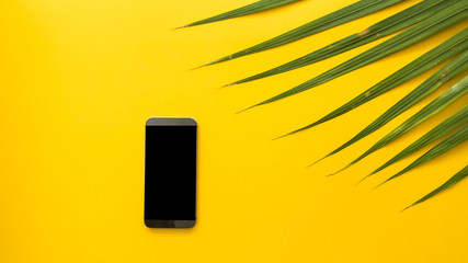 Wall Mural - Leaves and smart phone on yellow background top view workspace