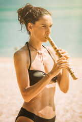 Young woman playing bamboo flute on the beach