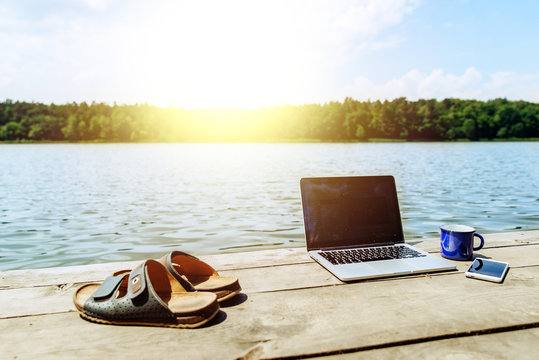 laptop with cup and phone one wooden dock. river on background. summer time. work with you