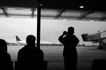 Black and white picture of family waiting their flight at international airport. Child takes photo of huge plane through window of terminal.