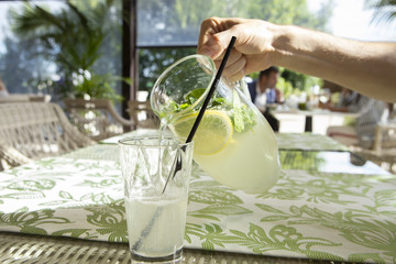 Lemonade with lemon, mint and ice. Young man pouring lemonade into glass.