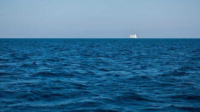 Blue sea with sailboat