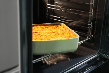 Baking tray with spinach lasagna in oven
