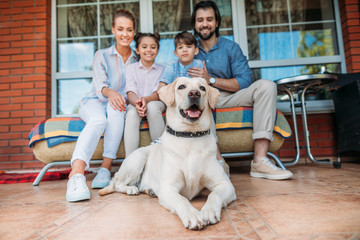 smiling family with labrador dog sitting on sofa together on country house porch