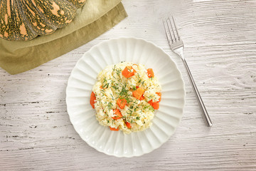Plate with delicious pumpkin risotto on wooden table