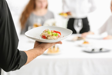 Waiter holding plate with salad at banquet, closeup