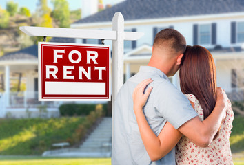 Military Couple Looking At House with For Rent Real Estate Sign In Front