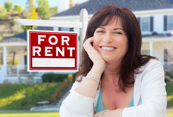 Middle Aged Woman In Front of House with For Rent Real Estate Sign In Yard